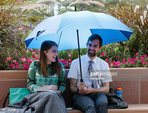 Two people avoid the rain under an umbrella between session of the 185th Semiannual General Conference of the Mormon Church on October 3 2015 in Salt...