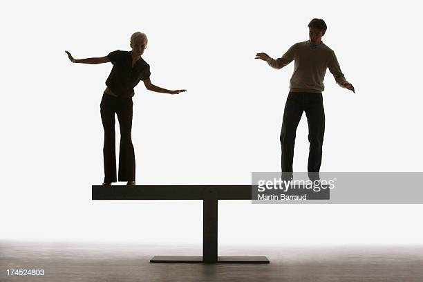 Two people balancing on top of a plank