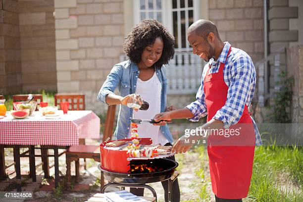 Two people barbecuing on the grill