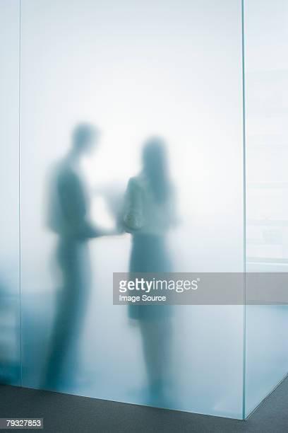 Deux personnes derrière une paroi en verre dépoli