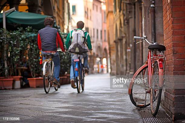 Two people bicycling in Pisa, Italy