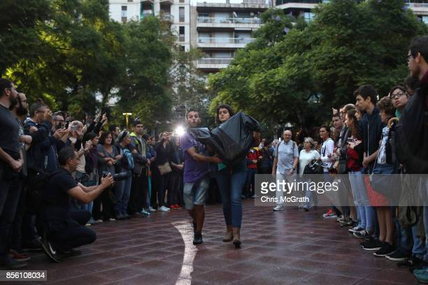 Two people bring in ballot boxes as crowds gather outside Escola Industrial of Barcelona school in protest and defence of the polling station from...
