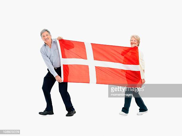 Two people carry the Danish flag