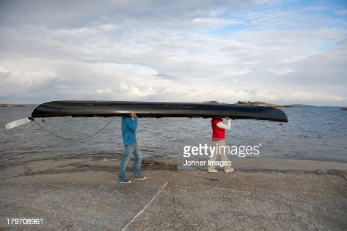 Two people carrying canoe at sea : Stock Photo