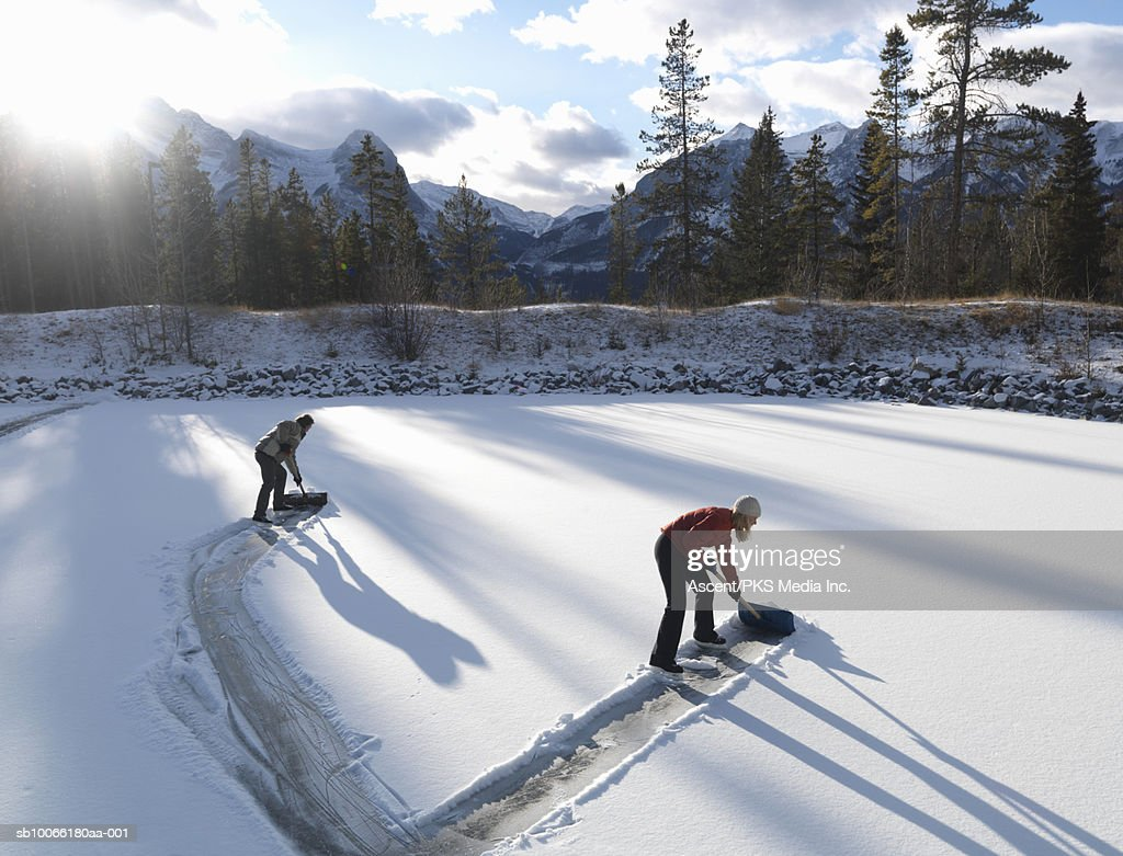 Two people clearing skating rink with shovels : Stock Photo