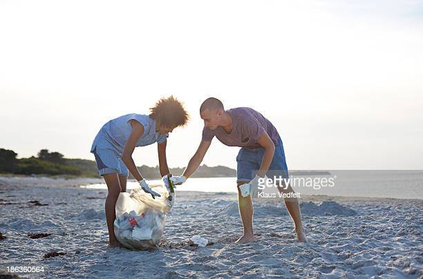 Two people collecting trash on beach