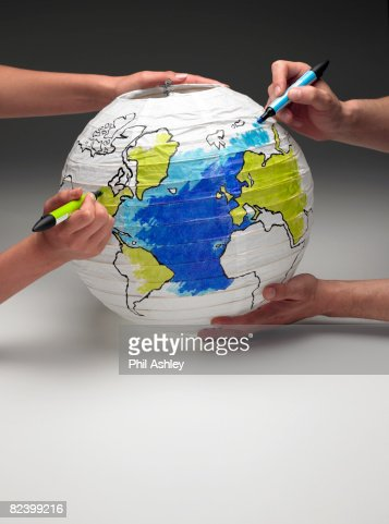 two people coloring in a globe lamp : Stock Photo