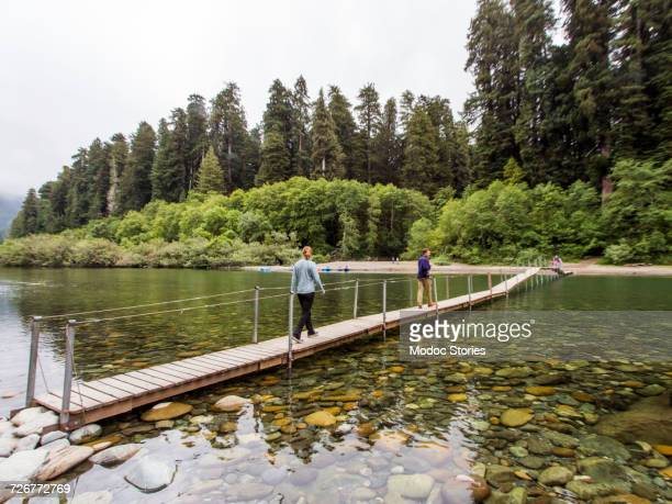 Two people cross a small bridge over the Smith River in Californias Redwoods National Park.