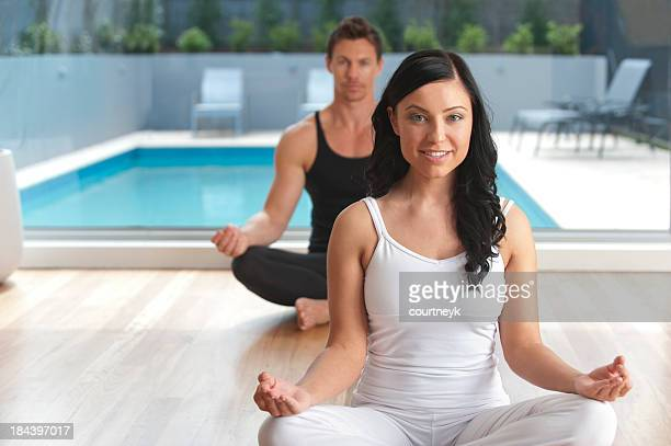 Two people doing yoga at a health club