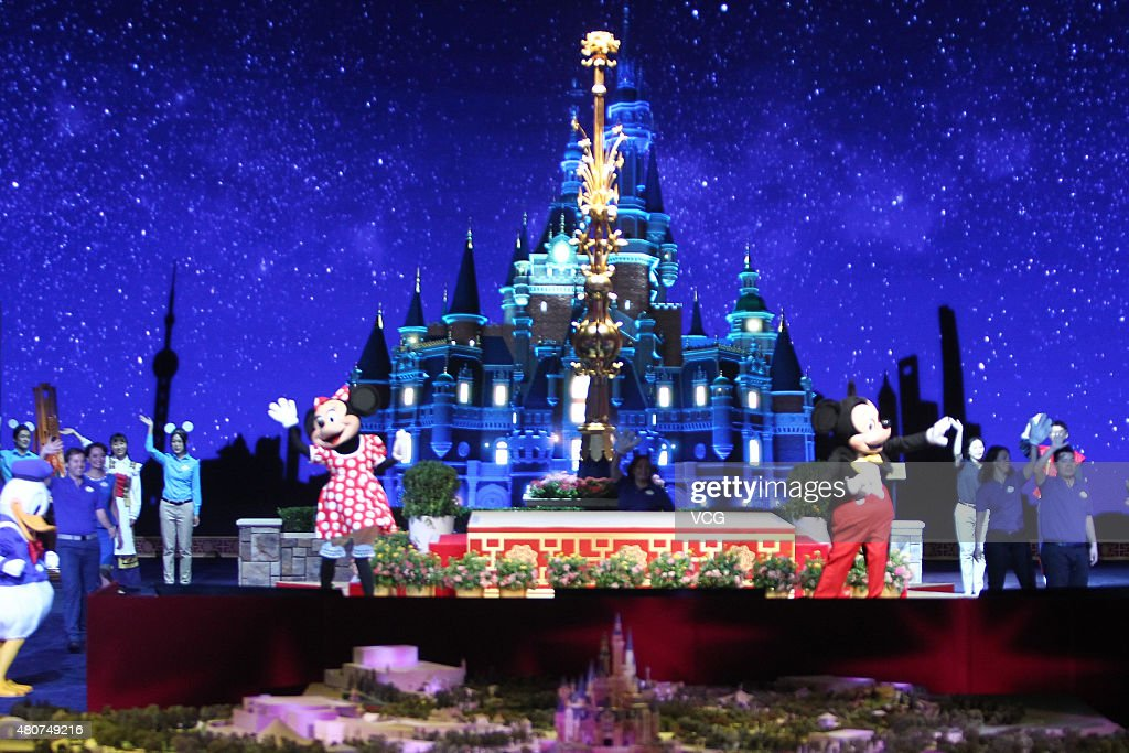 Two people dressed as Mickey Mouses perform on the stage during the unveilling ceremony of six themed parks of Shanghai Disney Resort at Shanghai...