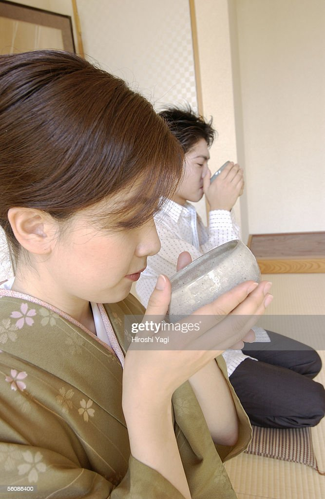 Two people drinking a cup of green tea : Stock Photo