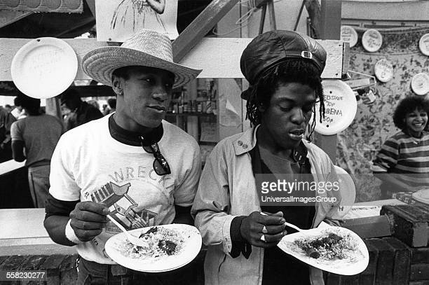 Two people eating jerk chicken and rice at a food stall Notting Hill Carnival London UK 1983
