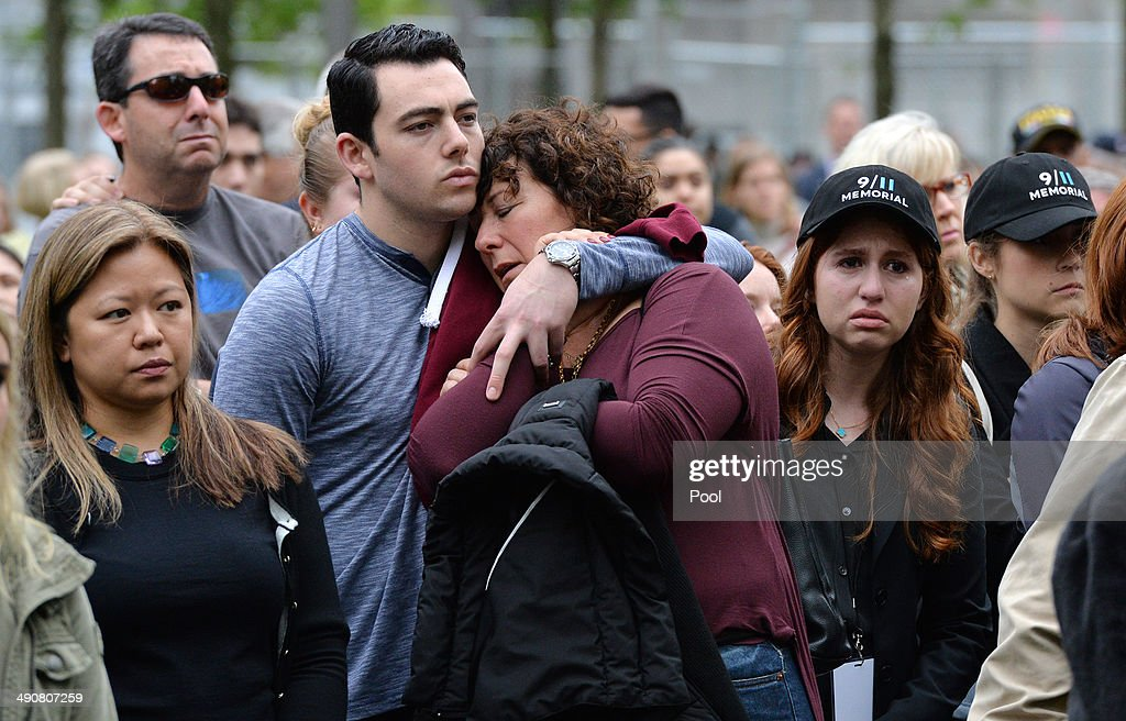 Two people embrace while gathered on the plaza of the National September 11 Memorial to watch the telecast of the dedication ceremony for the museum at ground zero May 15, 2014 in New York City. The museum spans seven stories, mostly underground, and contains artifacts from the attack on the World Trade Center Towers on September 11, 2001 that include the 80 ft high tridents, the so-called 'Ground Zero Cross,' the destroyed remains of Company 21's New York Fire Department Engine as well as smaller items such as letter that fell from the hijacked plane and posters of missing loved ones projected onto the wall of the museum. The museum will open to the public on May 21.
