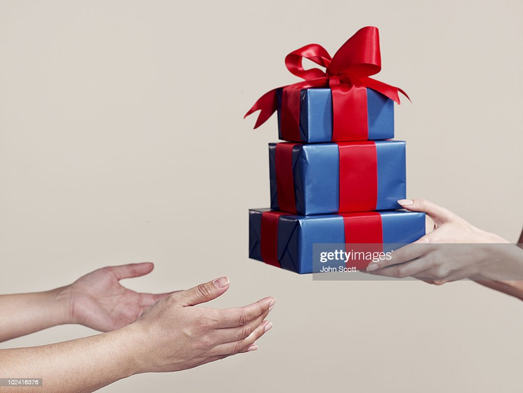 Two people exchanging gifts, close-up of hands : Stock Photo