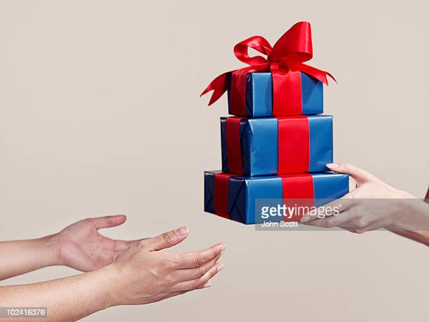 Two people exchanging gifts, close-up of hands