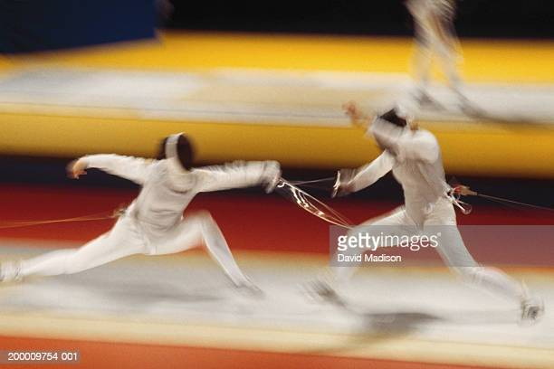 Two people fencing (blurred motion)