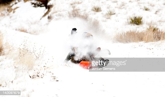 Two people getting hit with snow while sledding.