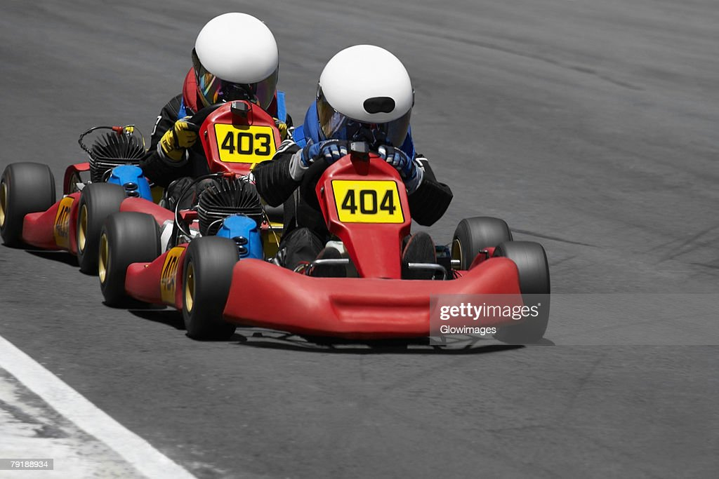 Two people go-carting on a motor racing track : Foto de stock