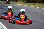 Two people go-carting on a motor racing track