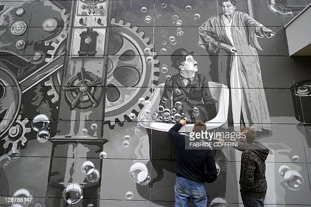 Two people have a close look during the official inauguration of two 40 meters high Gilamont towers adorned with giant frescos representing comic...