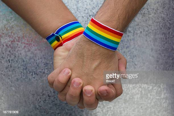 Two people holding hands and wearing rainbow bracelets