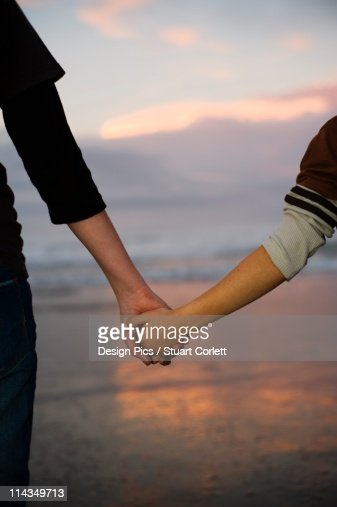 Two People Holding Hands On The Beach Stock Photo | Getty ...