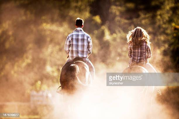 Two people horseback riding.