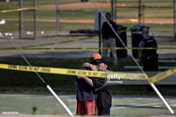 Two people hug in front of police crime scene tape following a shooting during a congressional baseball practice hug near the Eugene Simpson Stadium...