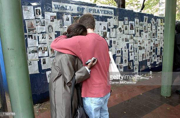 Two people hug in front of the Wall of Prayers for victims of the World Trade Center disaster September 14 2001 at Bellevue Hospital in New York City...