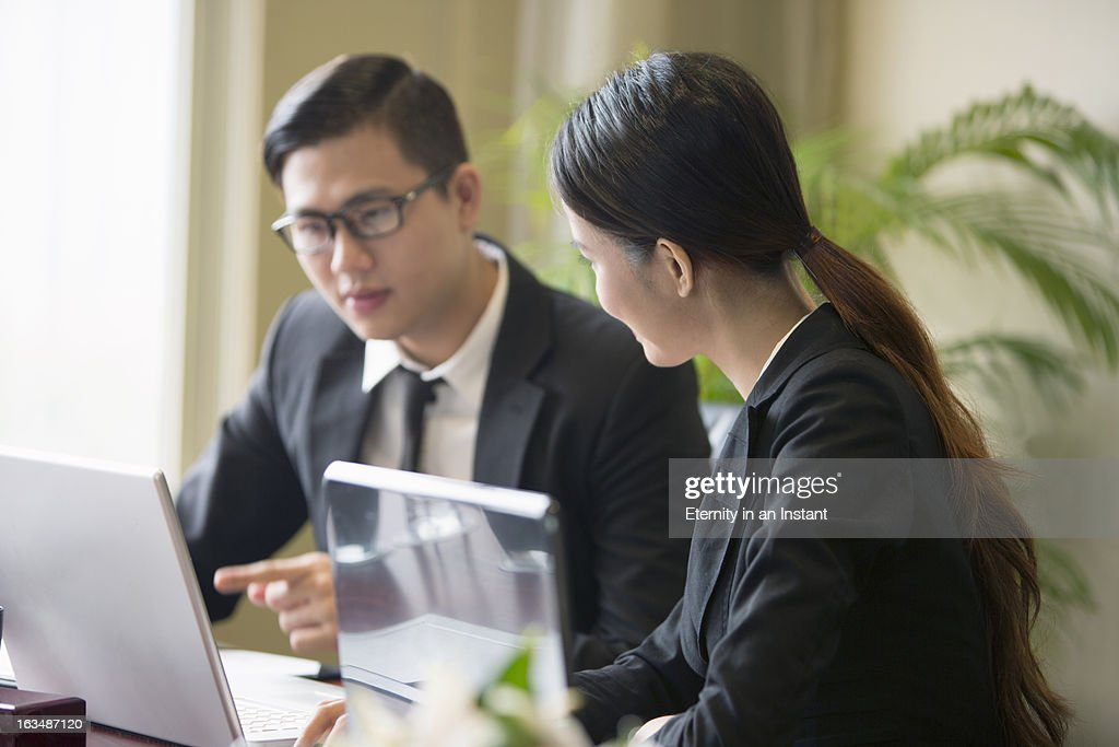 Two people in business meeting with laptops