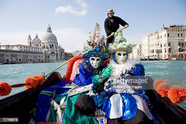 Two people in carnival costumes sitting in gondola, Venice, portrait