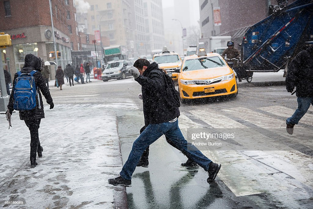 Two people jump over a puddle during a snowstorm that is moving through the Northeast on January 21, 2014 in New York City. Along with dropping arctic tempertures the storm is expected to bring three to five inches by nightfall, with another four to six inches falling overnight.
