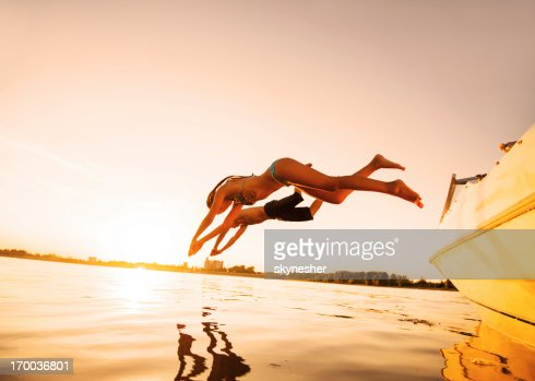 Two people jumping in water against the sunlight.