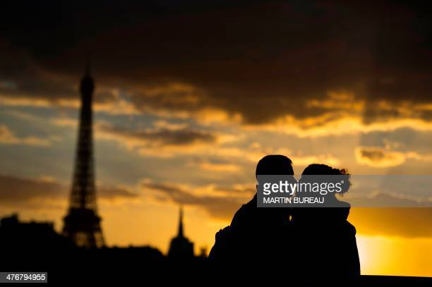 Two people kiss in front of the Eiffel Tower at sunset on March 5 2014 in Paris AFP PHOTO / MARTIN BUREAU / AFP / MARTIN BUREAU