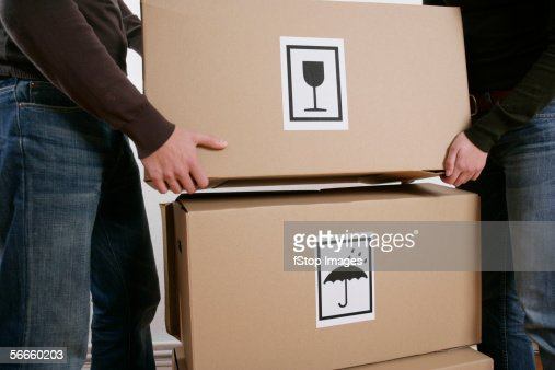 Two people lifting moving boxes : Stock Photo