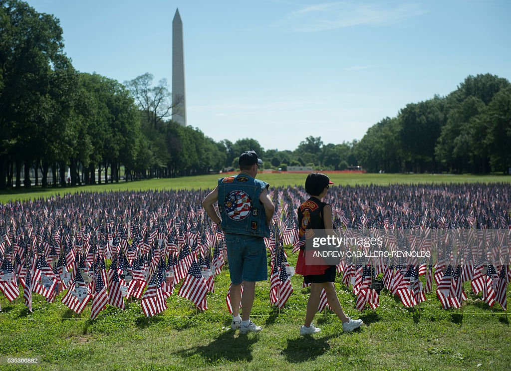 Two people look at flags representing fallen soldiers during the annual Rolling Thunder 'Ride for Freedom' parade ahead of Memorial Day in Washington, DC, on May 29, 2016. / AFP / Andrew Caballero-Reynolds
