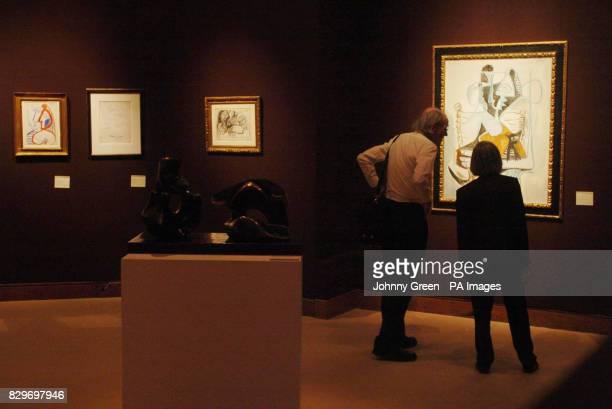Two people look at Pablo Picasso's 'Femme tenant un chat dans ses bras'