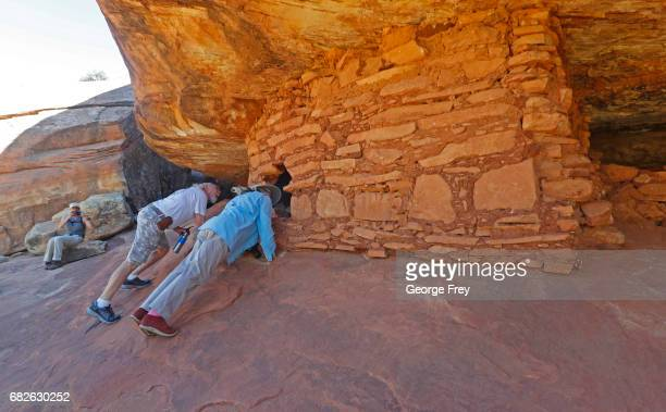 BLANDING UT MAY 12 Two people look inside an ancient granary part of the House on Fire ruins in the South Fork of Mule Canyon in the Bears Ears...