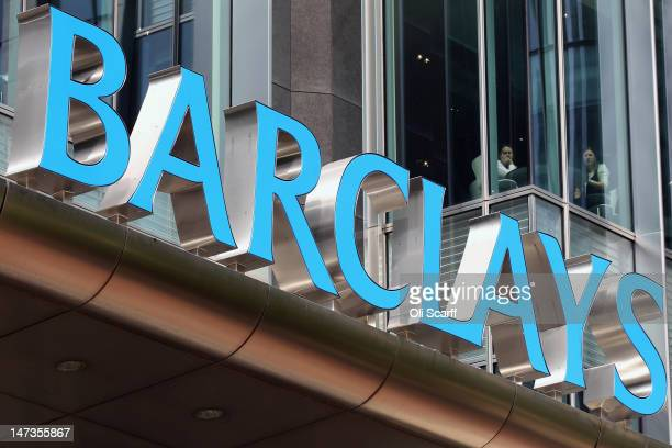 Two people look out from the Canary Wharf headquarters of Barclays Bank who have been fined 290 million GBP for manipulating the Libor interbank...