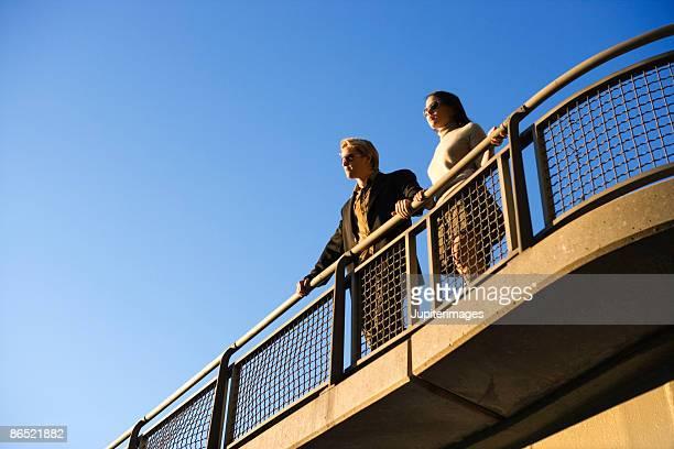 Two people looking over railing of bridge