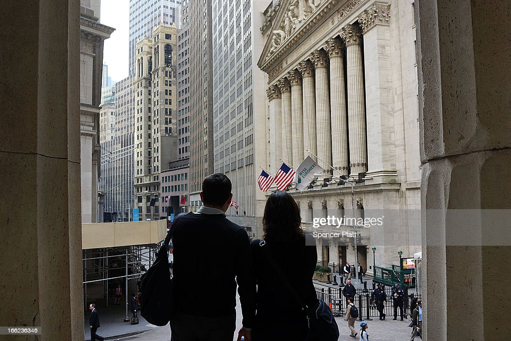 Two People looks out over the New York Stock Exchange at the end of the trading day on April 10, 2013 in New York City. The Dow Jones industrial average hit a new trading high of 14,826.66 Wednesday, moving up 0.9%.
