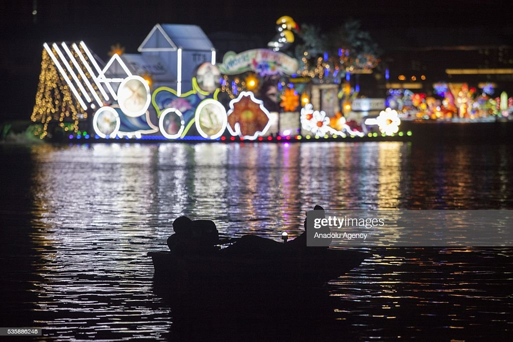 Two people on a boat watch the colorful decorated boats representing the states of Malaysia during the Magic Of The Night event at Royal Floria flower festival in Putrajaya, Malaysia on May 30, 2016.