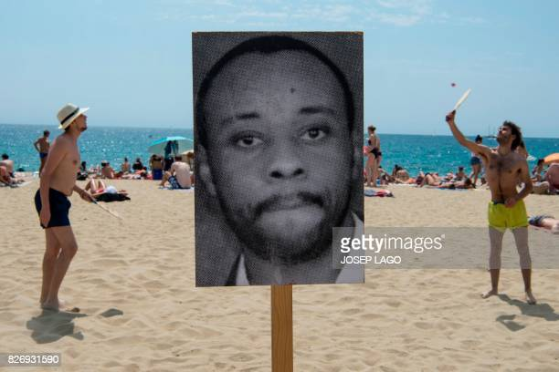 Two people play beach paddle ball on Barcelona's Bogatell beach behind a photograph of a dead migrant during an action called by pro human rights...