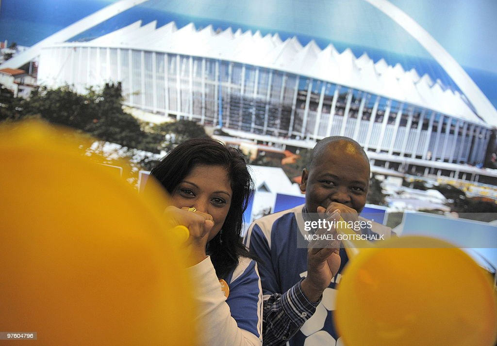 Two people poses for a photo while playing Vuvuzelas at South Africa's stand at the ITB travel trade fair at the fair grounds in Berlin on March 10...