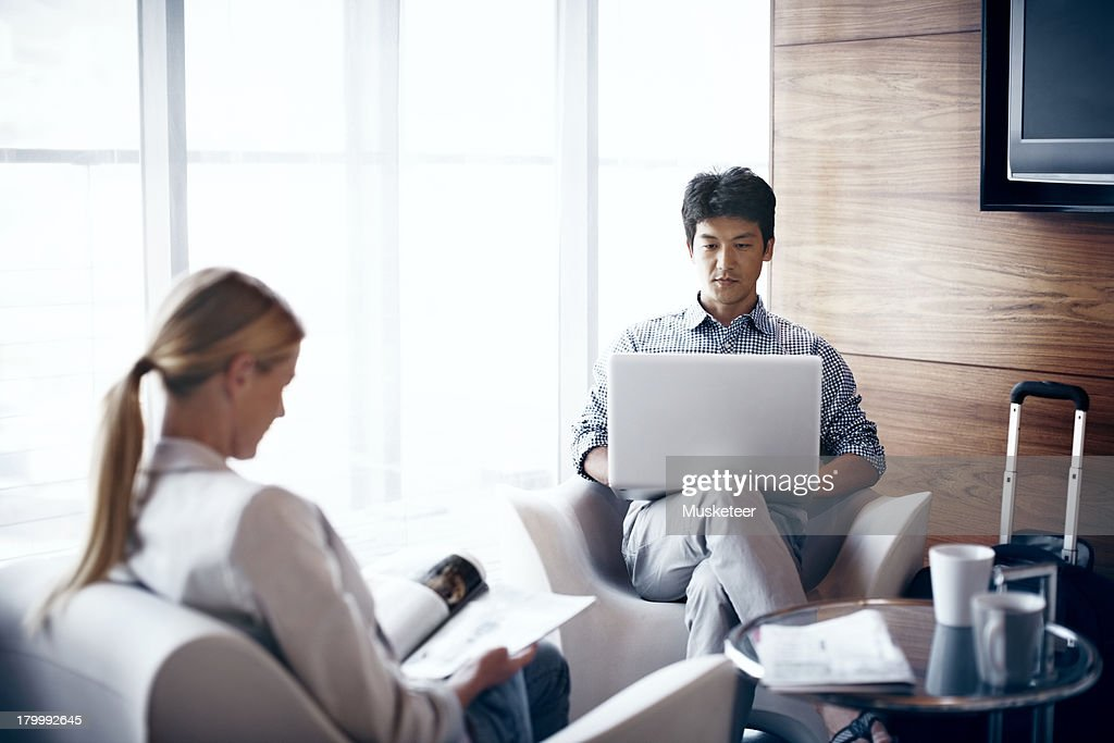 Two people relaxing in an airport lounge : Stock Photo