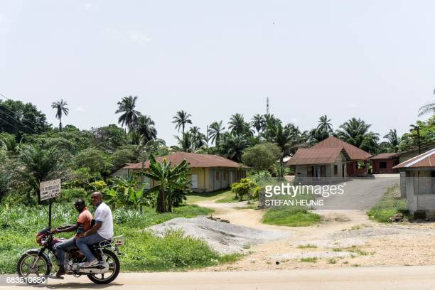 Two people ride a motorbike by houses of the Obung community on April 26 in Calabar through which the proposed Cross River Super Highway will run and...