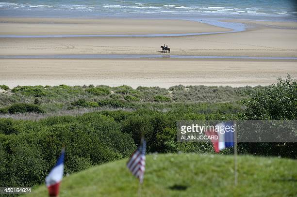 Two people ride horses on Omaha Beach during a joint FrenchUS DDay commemoration ceremony at the Normandy American Cemetery and Memorial in...