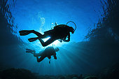 Two scuba divers silhouetted against the sun while they explore a coral reef