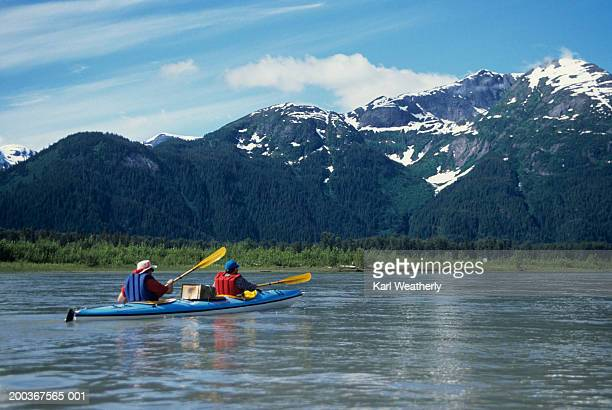 Two people sea kayaking on Stikine River, Alaska, USA, rear view