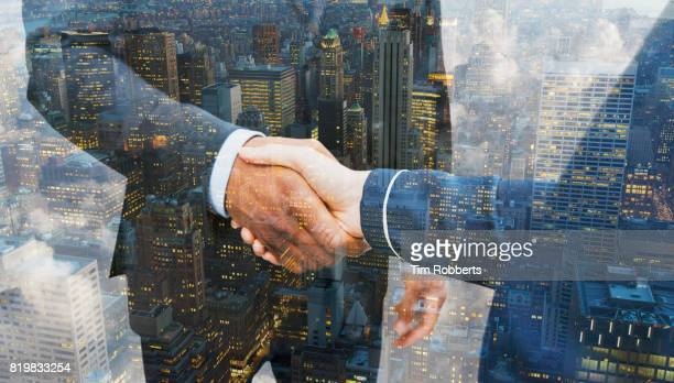 Two people shaking hands with buildings.